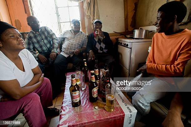 Men and women drink in a shebeen an illegal tavern usually in someone's home in Gugulethu on February 10 about 15Km from the centre of Cape Town The...
