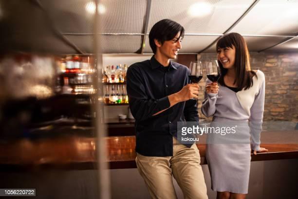 男性と女性は、バーで立って飲むカウンター - evening meal ストックフォトと画像