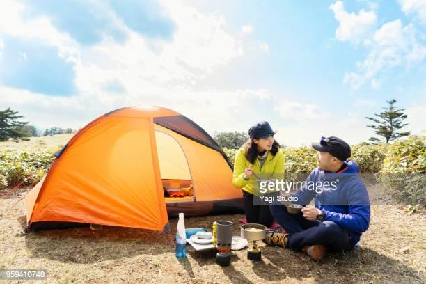 男性と女性は自然の中のキャンプでアウトドア クッキングを楽しむ - キャンプ ストックフォトと画像