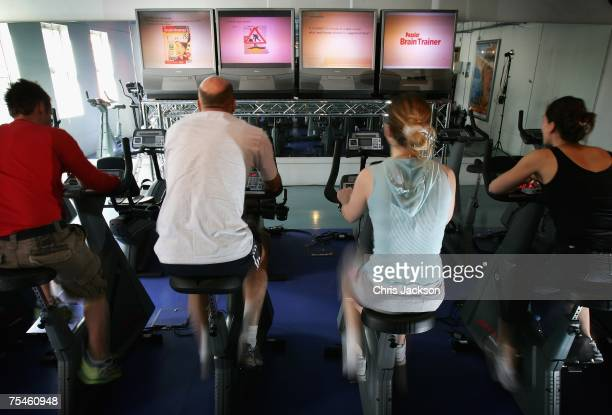 Men and women exercise in front of screens displaying puzzles and games as part of a full mind and body workout at the Fit Rooms on July 18 2007 in...