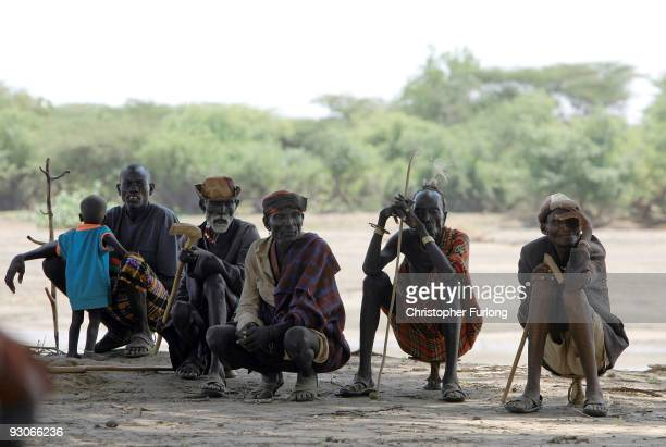 Men and women from the remote Turkana tribe in Northern Kenya wait their turn to see if they will be selected for food aid by other villagers at...