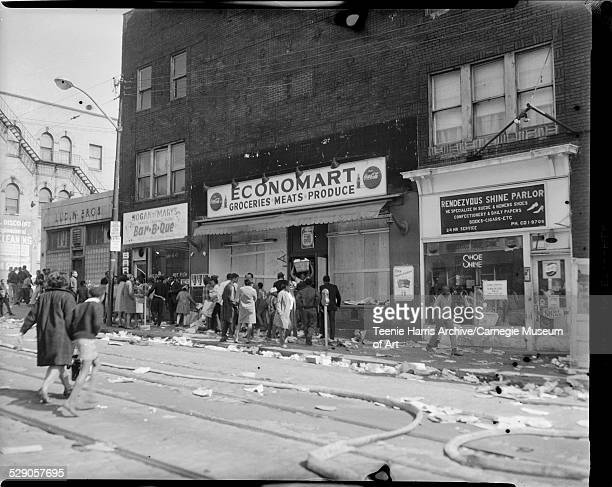 Men and women gathered outside Economart Market with broken windows Rendezvous Shine Parlor and Hogan and Mary's BarBQ with fire hoses in street...