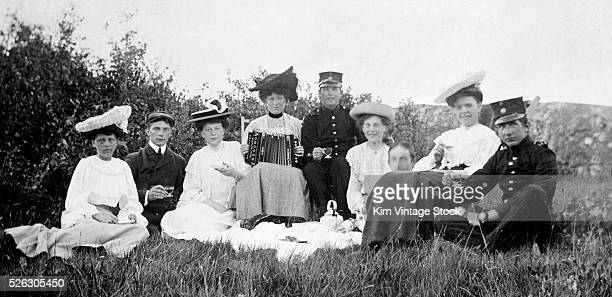 Men and women have a picnic out in a grassy meadow in Sweden