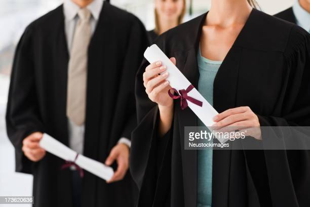 Men and women holding graduation certificates
