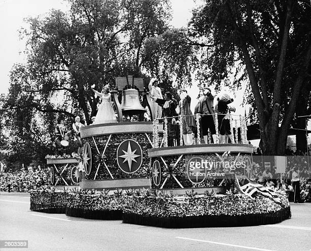 Men and women in 18th century costumes wave from atop a Liberty Bell float during an American Bicentennial parade, July 4, 1976.