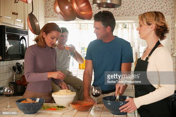 Men and women in kitchen preparing food