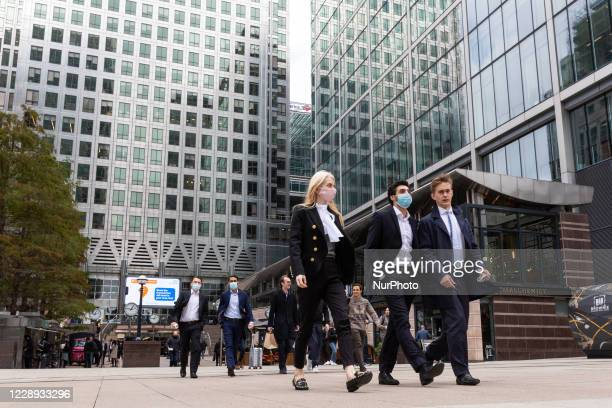 Men and women in protective face masksare seen during their lunch break at Canary Wharf financial skyscrapershub as the secondwave of Coronavirus...