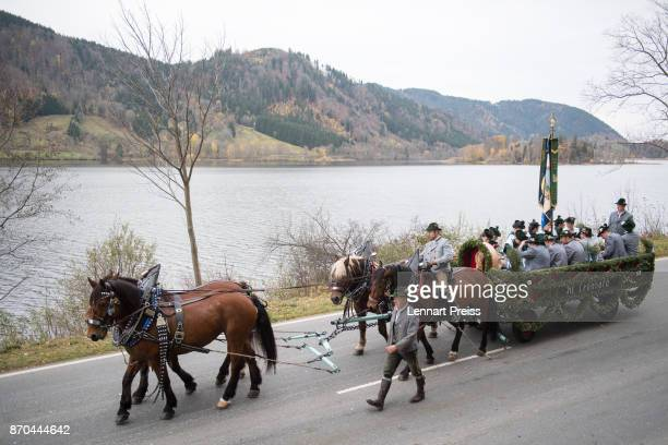 Men and women in traditional Bavarian folk dress ride a horsedrawn wagon during the annual Leonhardi procession along Schliersee lake on November 5...