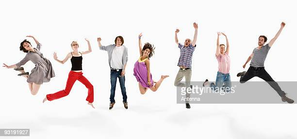 men and women jumping mid-air together - benen gespreid stockfoto's en -beelden