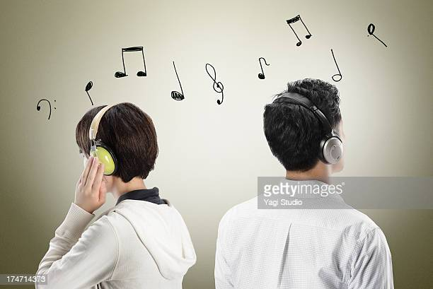 men and women listening to music - musical note stock photos and pictures