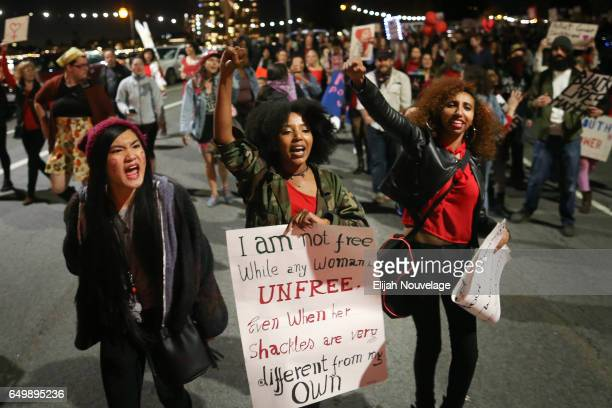 Men and women mark International Women's Day by taking part in a protest march through city streets on March 8 2017 in Oakland California Protest...