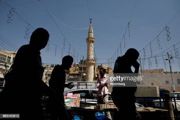 Men and women pass a street vendor in Amman Jordan on Thursday June 21 2018 President Trump and First Lady Melania Trump will host JordansKing...