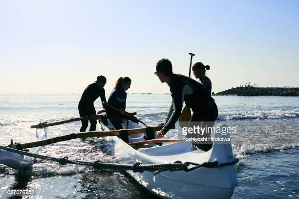 Men and women playing canoe at Pacific Ocean.