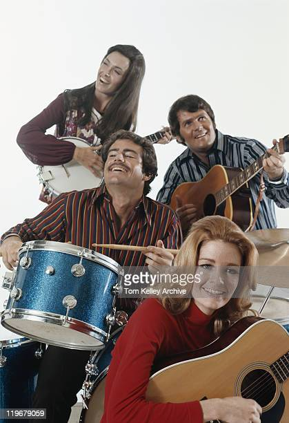 men and women playing guitar and drum, smiling - 1971 stock pictures, royalty-free photos & images