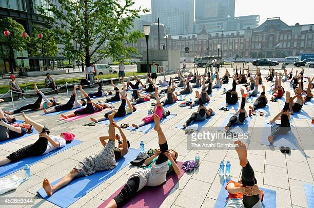 Men and women practice yoga in front of JR Tokyo Station on the morning of July 25 2014 in Tokyo Japan After laying down their colorful mats 93 women...