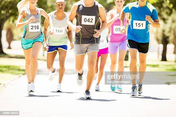 Los hombres y las mujeres corriendo maratón en el parque
