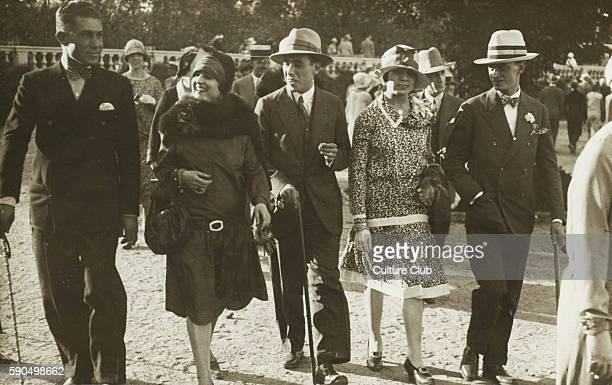 Men and women 's fashions 1923 A group takes an afternoon stroll possibly in Paris The men wear suits with bowties and hats and carry canes The women...