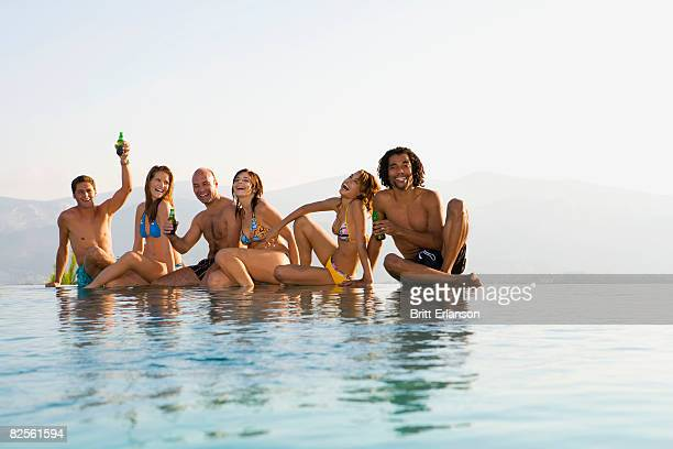 Men and women sitting by edge of pool