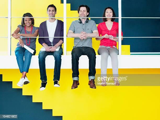 Männer und Frauen sitzen in einer Reihe an Sims