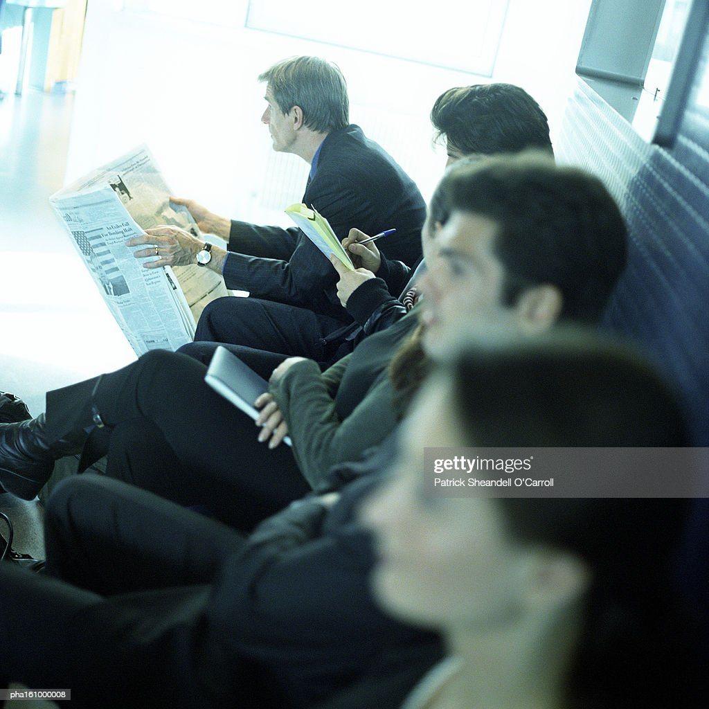 Men and women sitting together on bench, side view. : Stockfoto