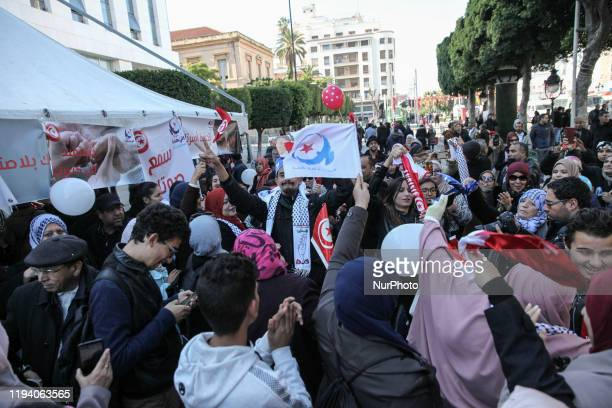 Men and women supporters of the moderate Islamist Ennahda party make the victory sign and raise flags of Ennahda as they dance on avenue Habib...