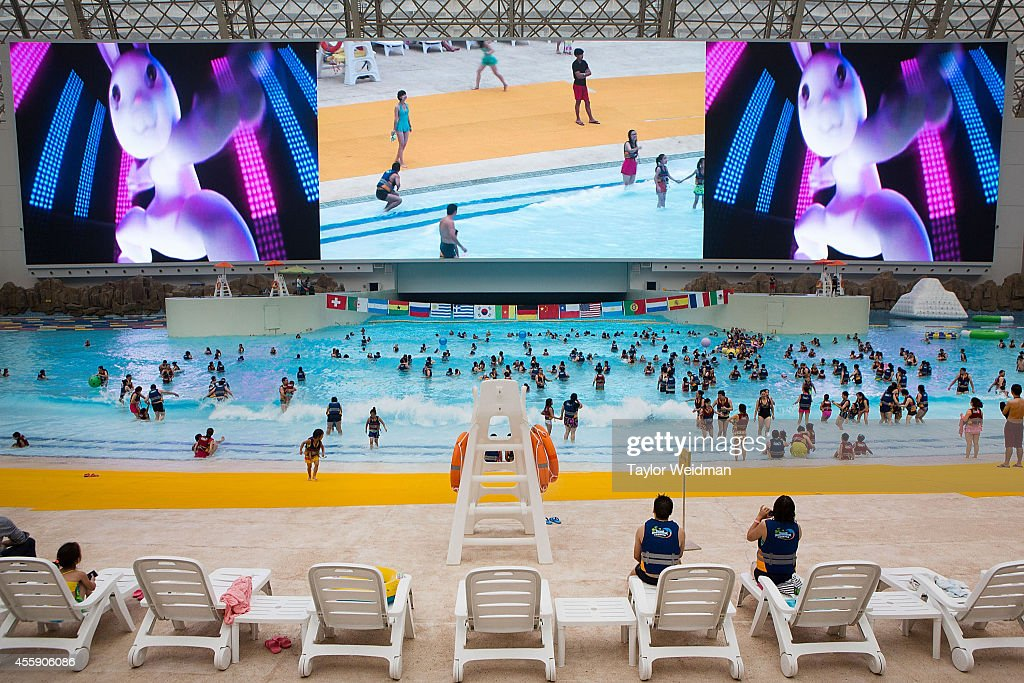 Men and women swim in the wave pool at the Paradise Island Water Park on September 20, 2014 in Chengdu, China. The Paradise Island Water Park is located inside of the New Century Global Center, the world's largest building measured by floor space, boasting 18,000,000 square feet of floor space.