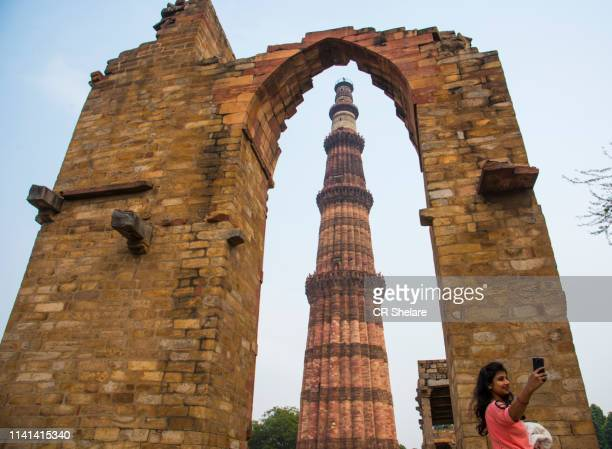 men and women taking photos in front of qutub minar. - sincerely yours ストックフォトと画像