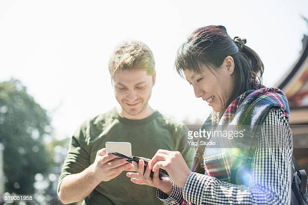 men and women using a smartphone in japanese shrine - shrine stock pictures, royalty-free photos & images