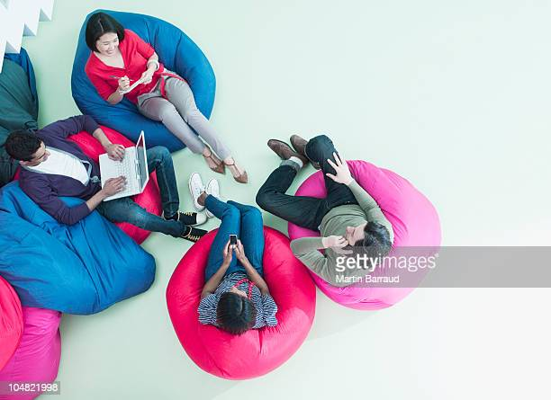 men and women using laptop and cell phones in bean bag chairs - above stock photos and pictures