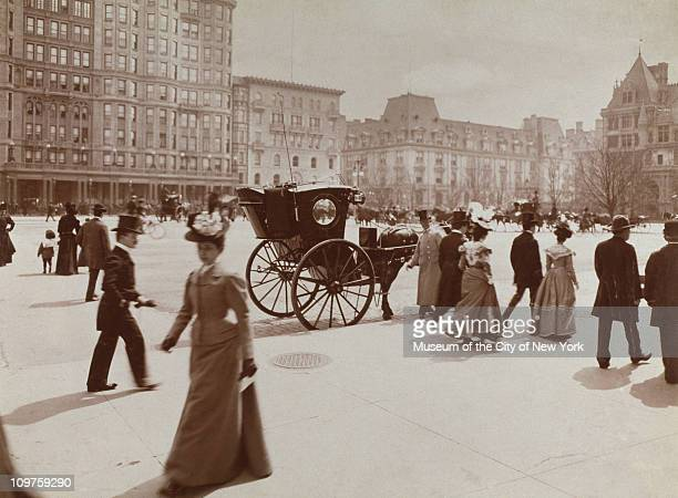 Men and women walk on Fifth Avenue in front of the Plaza Hotel between 57th and 59th Streets as a horsedrawn carriage sits by the curb New York City...
