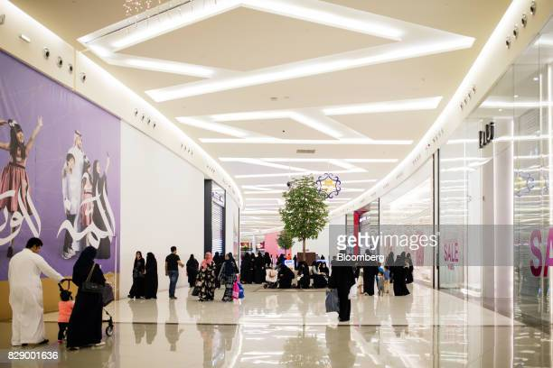 Men and women walk past closed stores including a Zara clothing store operated by Industria de Diseno Textil SA right during prayer time at the Al...