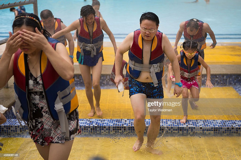 Men and women walk through a mandatory showering area after visiting the wave pool and artificial beach at the Paradise Island Water Park on September 20, 2014 in Chengdu, China. TThe Paradise Island Water Park is located inside of the New Century Global Center, the world's largest building measured by floor space, boasting 18,000,000 square feet of floor space.