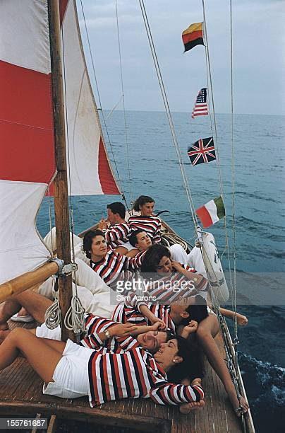 Men and women wearing red white and blue striped tops relaxing on a small boat with a red and white mast and small flags of Germany USA Great Britain...