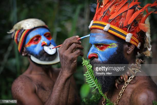 Men apply face paint for festival
