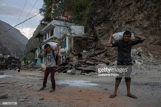 Men are carrying their last rice bags as they gonna share with other villagers on the Araniko Road near the Kobani Village Isolated Nepalese...
