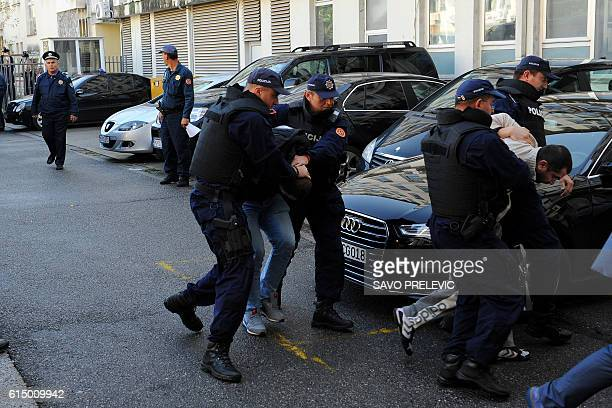 Men are escorted by Montenegrin police officers to the special court in Podgorica on October 16 2016 Montenegro said it had arrested 20 Serbs for...