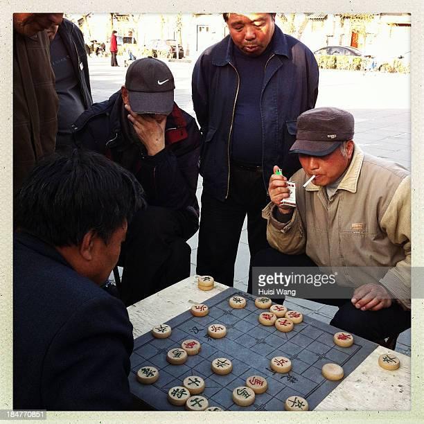 Men are playing Xiangqi near Gulou , in Beijing, China. The photo was taken on April 11, 2013.