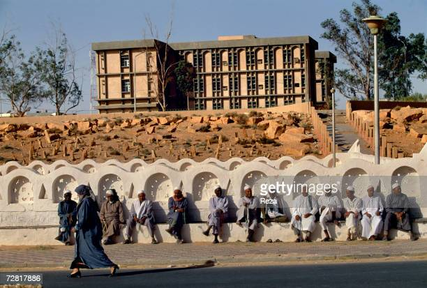 Men are seated during a funeral for a last prayer to the dead at the cemetery in front of a new building of the modern town April 2000 in Ghadames...