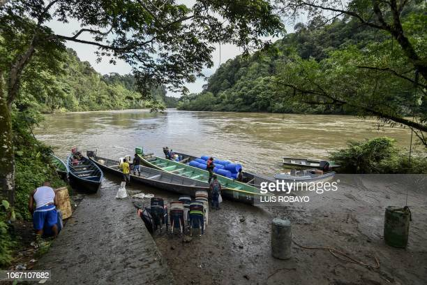Men are seen next to boats in a pier on the Mira river in Vallenato rural area of the municipality of Tumaco department of Narino in the southwest of...