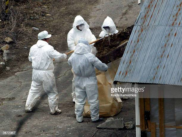 Men are seen working at Win-Win Farm, a poultry farm where bird flu has been found on January 16, 2004 in the town of Ato, Yamaguchi Prefecture,...