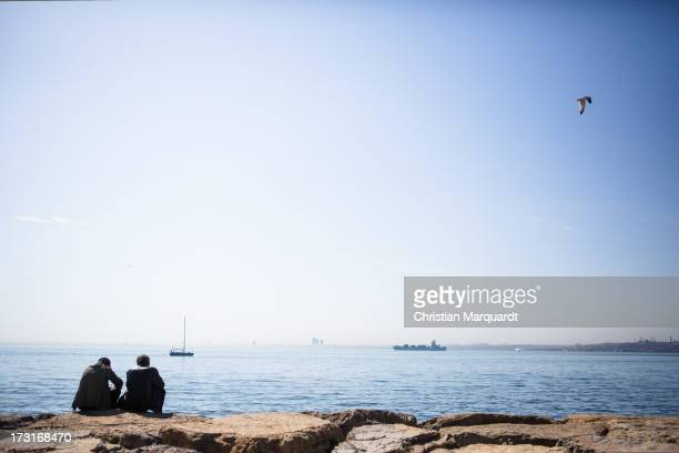 Men are sitting on the shore and looking at the Sea of Marmara April 13 2013 in Istanbul Turkey