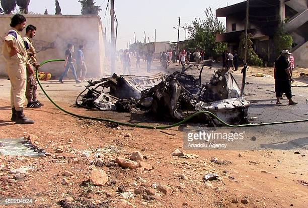 Men are trying to extinguish a burning after wehicle after a USled coalition forces airstrike targeting Al Nusra members in Kafer Hend village of...