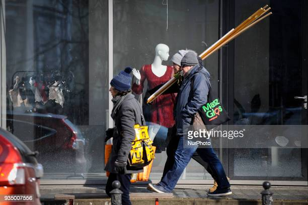 Men are with biulding materials are seen walking past a mannequing in a shop window in Warsaw Poland on March 17 2018