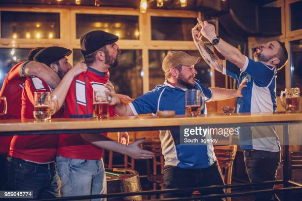men arguing in sports pub - hooligan stock pictures, royalty-free photos & images