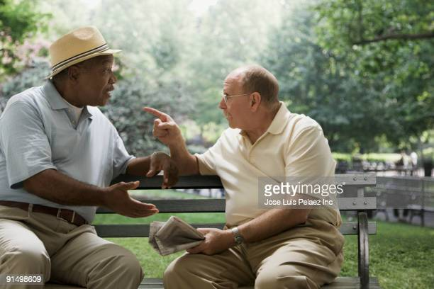 Men arguing on park bench