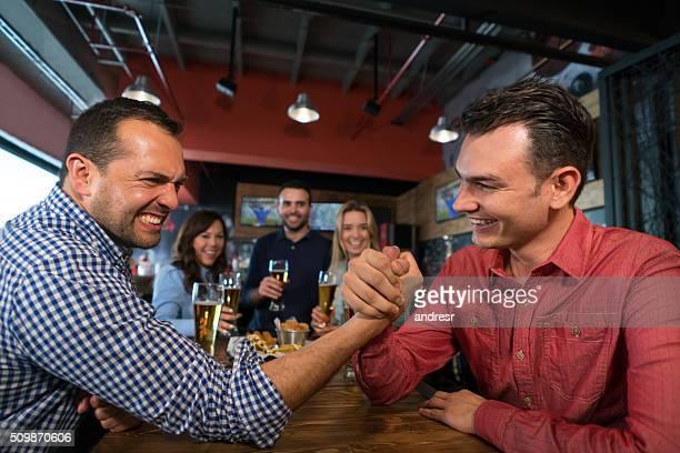 Men arm wrestling at a bar