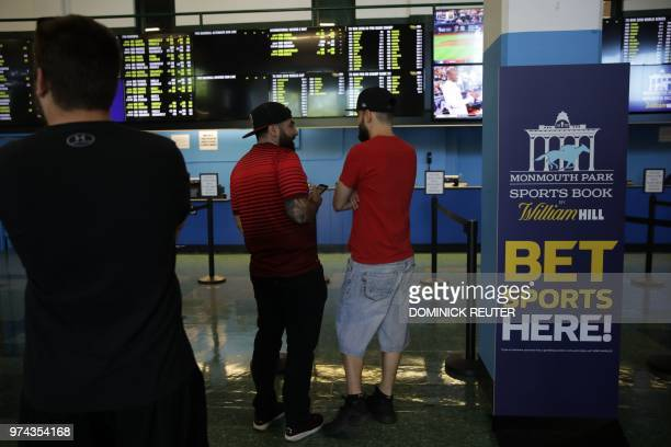 Men arrive to place their bets at the Monmouth Park Sports Book on the first day of legal sports betting in the state in Monmouth Park in Oceanport...