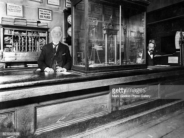 Men at bank counter, late 1900s.
