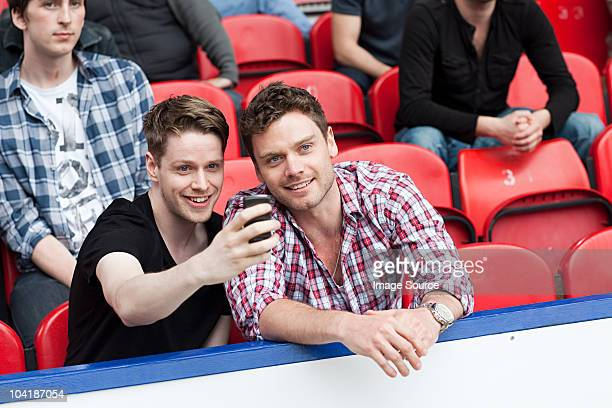 Men at football match with camera phone
