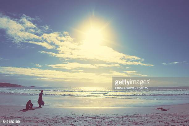 men at sea shore on sunny day against sky - frank swertz stock pictures, royalty-free photos & images